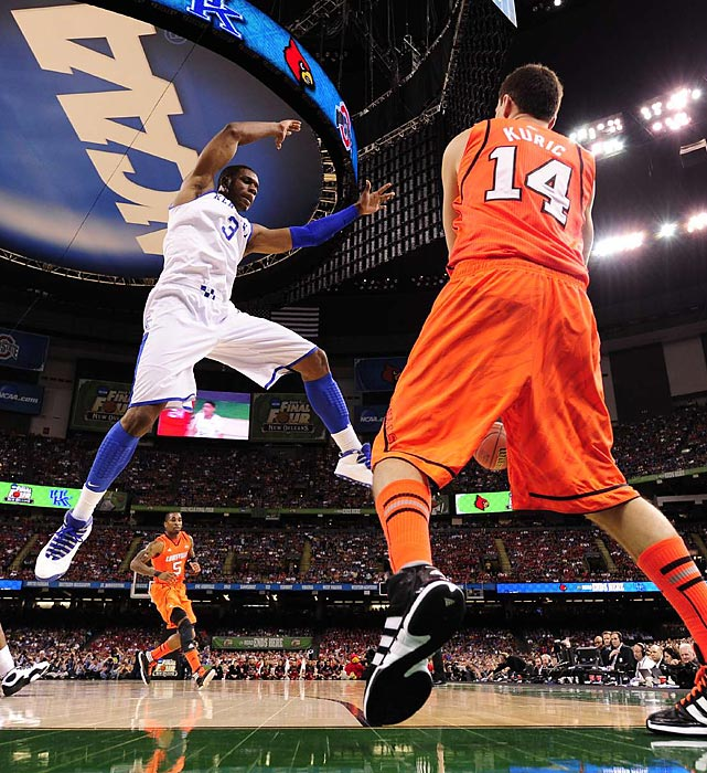 Louisville's Kyle Kuric passes the ball around the leaps of Kentucky's Terrence Jones.