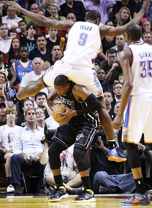 Oklahoma City Thunder's Serge Ibaka (9) lands on top of Dwyane Wade during the second half of the Miami Heat's eventual 98-93 win.