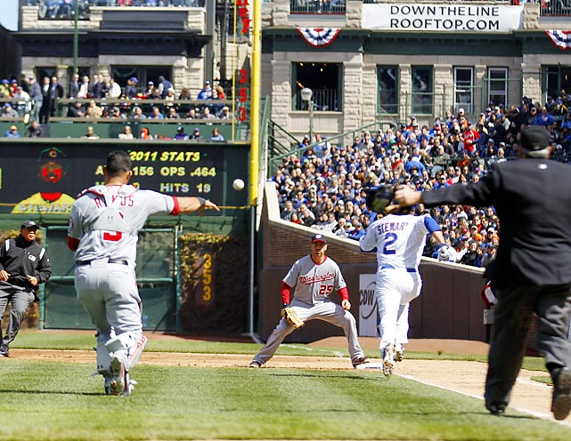 Nationals catcher Wilson Ramos throws to Adam LaRoche as the Cubs' Ian Stewart charges down down the first base line.