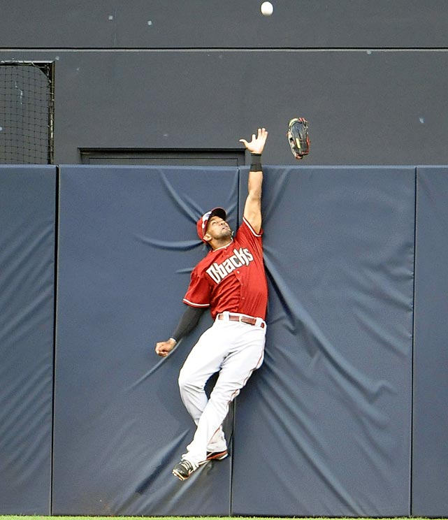 Arizona Diamondbacks' Chris Young loses his glove over the wall as he tries to prevent a two-run homer by San Diego's Chris Denorfia.