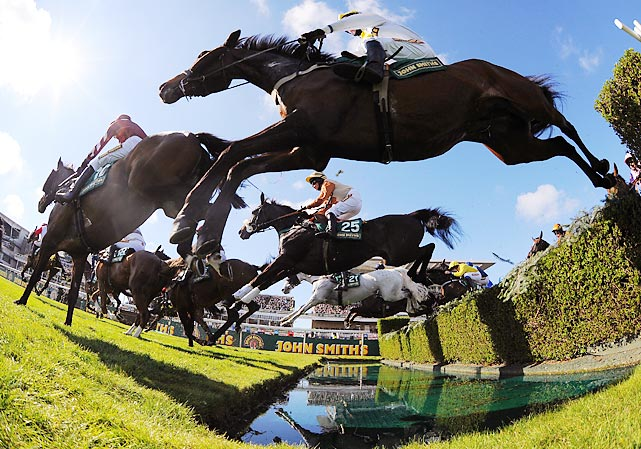 Horses leap over the water jump during the Fox Hunters Steeple chase during the first day of the Grand National horse racing meeting. The meeting ends Saturday with the Grand National, which is the biggest betting race in the United Kingdom.