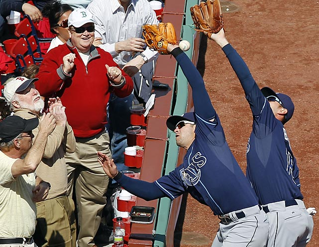 Red Sox fans look on gleefully as Tampa Bay's Evan Longoria (left) and Reid Brignac fail to catch a foul ball.
