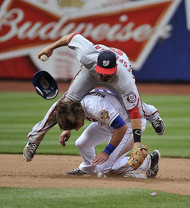 Washington Nationals second baseman Danny Espinosa trips over  a semi-sliding Kirk Nieuwenhuis of the New York Mets.