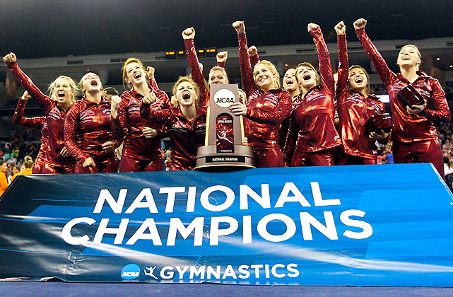 Alabama gymnasts pose with the trophy after winning the NCAA women's gymnastics championships.