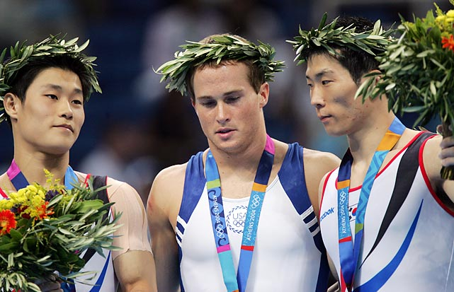 "At the 2004 Games in Athens, Paul Hamm (center) became the first American to ever win the gymnastics all-around title, but it wasn't that simple. After a blunder on the vault, Hamm fought his way back onto the medal podium in what Peter Vidmar -- the only other American male to ever win an all-around medal -- called, ""[The] greatest comeback in the history of gymnastics."" It was later revealed, however, that the FIG mis-scored fellow competitor Yang Tae Young's routine, bringing Hamm's gold into question. Two months and countless appeals later, the Court of Arbitration for Sport ruled that the gold was rightfully Hamm's. He was relieved. ""There's been a lot of fighting for this medal,"" he said. ""I think it'll mean that much more, that I'll be able to keep it for the rest of my life."""