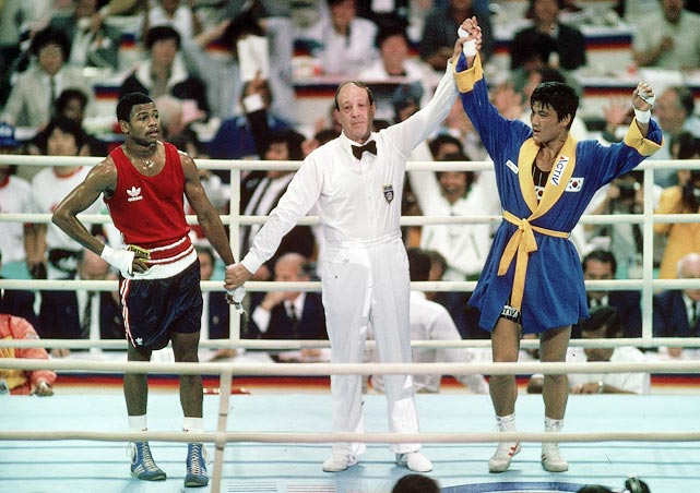 "There's little doubt that Roy Jones Jr. was the best boxer at the 1988 Olympics in Seoul, South Korea. Jones, then 19, dominated South Korea's Park Si Hun in the final, landing 86 punches to Park's 32, but at the end of the match it was Park, not Jones, who was named the gold medalist in a 3-2 decision. Jones was stunned by the decision. Later, the three boxing judges were given two-year bans (two were later banned for life), and Jones was awarded the Val Barker Cup as the outstanding boxer of the Olympics, but it was all of little consolation to Jones. ""That's the worst I've ever been dealt in my life,"" he said. ""They put the silver medal around my neck, and I took it right off. I won't put it around my neck ever again."""