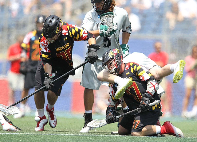 A Maryland player upends a Loyola player while fighting for ball possession.