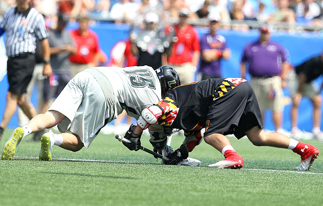 Loyola and Maryland players fight for the ball during a face off.