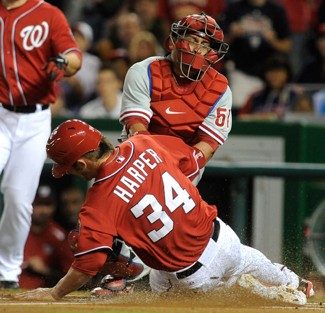 Harper slides safely after stealing home base against Phillies pitcher Cole Hamels. Harper had reached base after being hit by Hamels, which the pitcher later admitted was intentional.