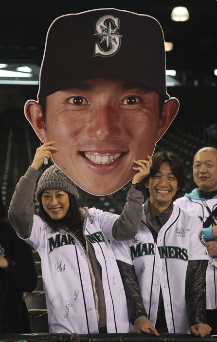 Mariners fans hold a giant cutout of Munenori Kawasaki prior to a game against the Rangers earlier this season.