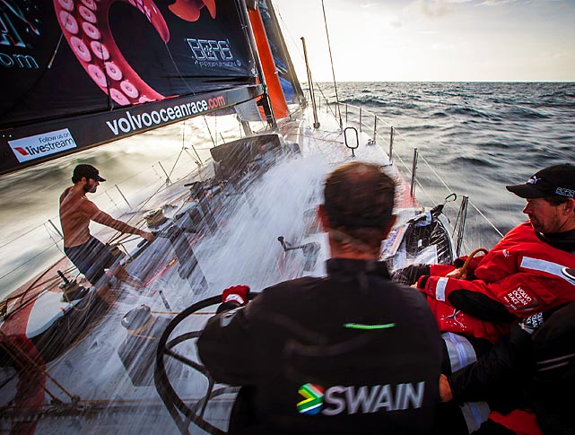 Water sprays across the deck and a shirtless crew member onboard PUMA Ocean Racing powered by BERG as the boat flies from Itajai, Brazil, to Miami during the sixth leg of the Volvo Ocean Race.
