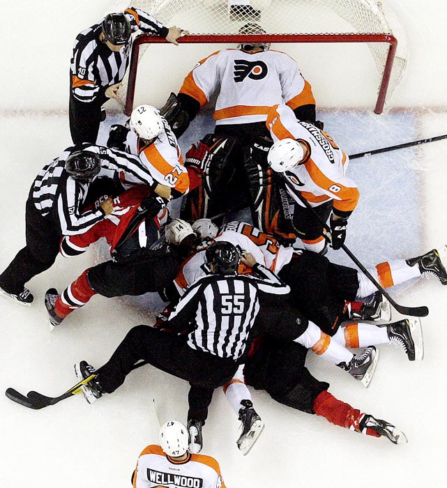 Philadelphia Flyers goalie Ilya Bryzgalov is on his back after making a save as officials pull apart a pile of players during Game 4 of a second-round NHL  playoff series.