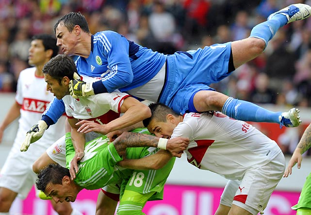 Wolfsburg forward Mario Mandzukic is nearly taken down by three other players, including his own goalie, while trying to prevent a goal during the first division Bundesliga football match between VfB Stuttgart and VfL Wolfsburg.