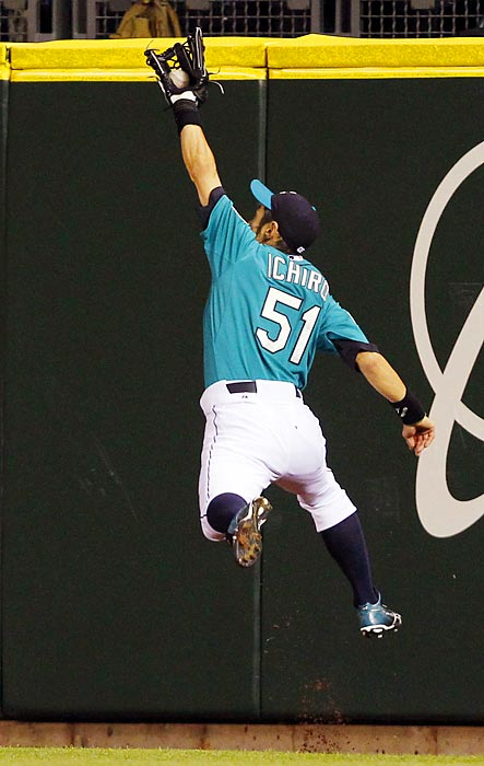 Seattle Mariners right fielder Ichiro Suzuki leaps to successfully snag a fly ball off the bat of Minnesota Twins' Danny Valencia.