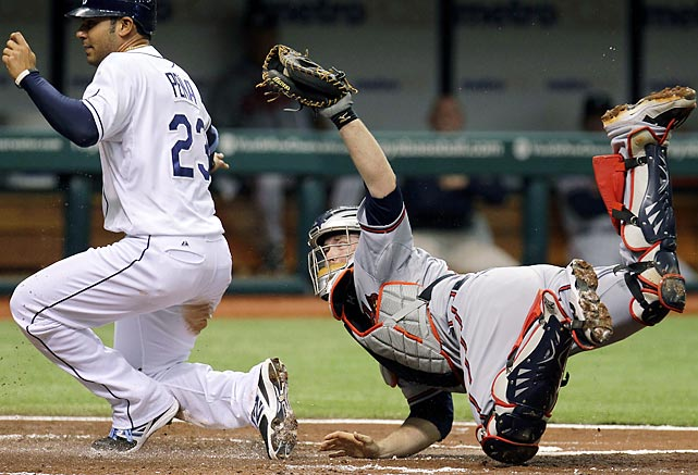 Atlanta Braves catcher Brian McCann tags out Tampa Bay Rays' Carlos Pena at home plate after Pena tried to score on Will Rhymes' second-inning fly-out.