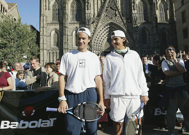 Love the reversed snap-hats. At a Babolat-sponsored event, Nadal and Carlos Moya play tennis in front of the Barcelona Cathedral.