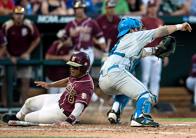 Devon Travis slides around UCLA's Tyler Heineman for a fourth-inning run as the Seminoles prevailed in a Bracket One elimination game. Florida State (50-16) plays Arizona on Thursday, needing to beat the Wildcats twice to reach the championship round. No. 2 national seed UCLA (48-16) was knocked out a day after No. 1 Florida was eliminated from the opposite bracket.