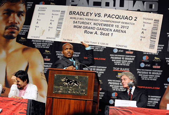 Bradley  holds up an oversize fake ticket   during Wednesday's news conference, already predicting a rematch with Pacquiao.