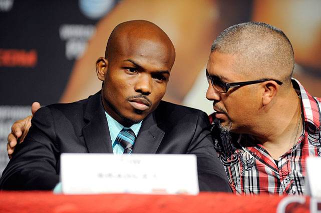 Bradley speaks with his trainer at Wednesday's final press conference at the MGM Grand's Hollywood Theatre.