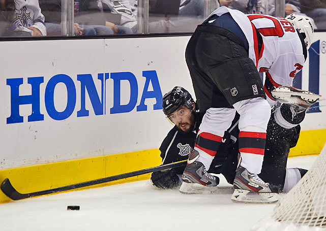 Kings defenseman Drew Doughty is knocked to the ice by Ryan Carter of the Devils.