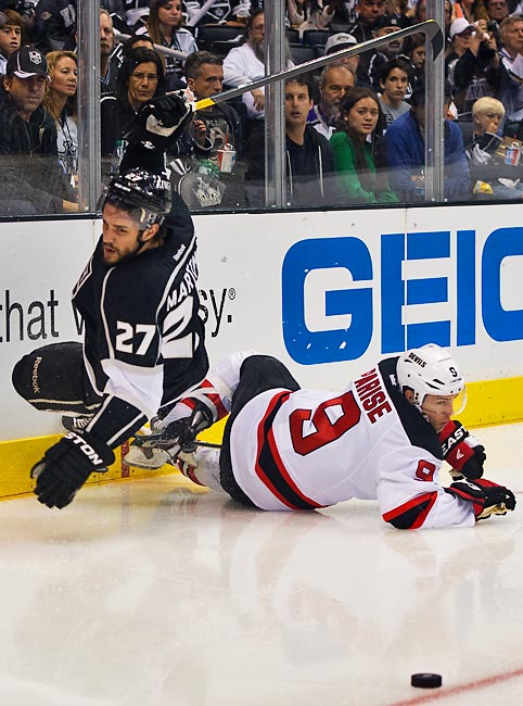 Alec Martinez and Zach Parise get tangled up along the end boards.