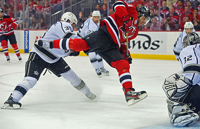 With a little help from Willie Mitchell, Devils forward Dainius Zubrus gets airborne in front of Kings goalie Jonathan Quick.