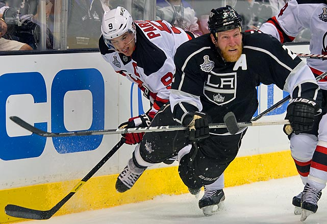 Kings defenseman Matt Greene falls to the ice after getting wrapped up with Devils forward Zach Parise.