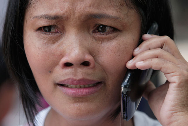 Filipino government volunteer librarian Gina Tubo cries during an interview after watching a free live public viewing Saturday's Manny Pacquiao-Timothy Bradley fight at a park in Marikina, east of Manila, Philippines.