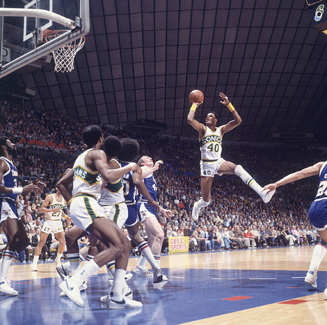 The 7-foot Marvin Webster shows of his game as he soars across the key at home against the Denver Nuggets.  Webster averaged 14 points during his only season with Seattle.