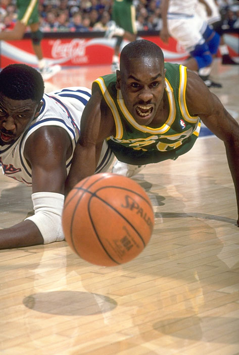 "Supersonics guard Gary Payton dives for a loose ball against the Sacramento Kings.  ""The Glove"" was known for his superb defensive abilities and his hustle on the court."