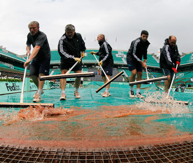 Part of the men's quarterfinals were delayed for rain and the women's semifinals were started late due to a flash rain storm. The court was covered with a tarp, squeegeed and play was able to start shortly after the rain let up. Stellar work from the ground crew.
