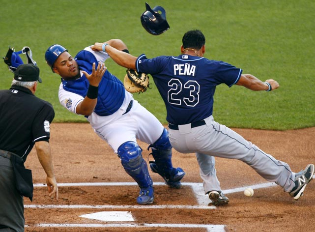 Carlos Pena of the Tampa Bay Rays separates Kansas City Royals catcher Brayan Pena from the ball before he touches home plate on June 26.  The Royals would go on to win 8-2.