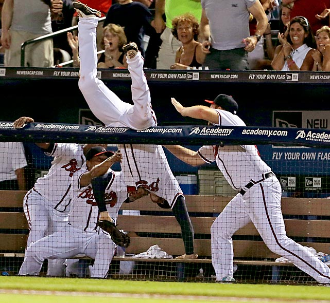 Atlanta first baseman Freddie Freeman goes head-over-heels into the Braves' dugout after catching an Alfonso Soriano foul ball.  The Cubs got the best of the July 4 matchup, defeating the Braves 5-1.