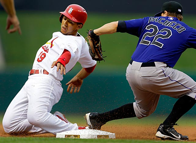 The Cardinals' Jon Jay safely steals third as he contorts his body away from Rockies third baseman Jordan Pacheco's tag.  St. Louis defeated Colorado 9-3 in their July 2 matchup.
