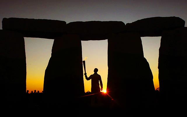 Olympic gold medalist and former sprinter Michael Johnson holds the Olympic Flame at Stonehenge at the beginning of day 55 of the London 2012 Olympic Torch Relay on July 12. The torch is making a 70-day relay involving 8,000 torchbearers covering 8,000 miles to get to London.