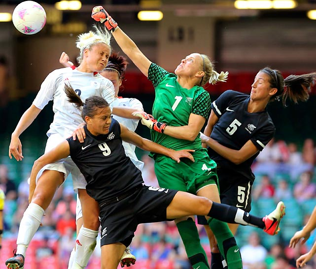 New Zealand goalkeeper Jenny Bindon punches the ball away from Britain's Stephanie Houghton's threatening head (left).  The host nation would go on to win the game 1-0, putting it in a tie for the top spot in Group E with Brazil.