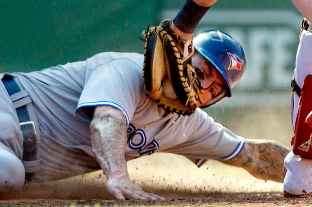 Toronto Blue Jays' Brett Lawrie slides safely into home before the tag from Red Sox catcher Jarrod Saltalamachia in the eighth inning at Fenway Park.  Red Sox starting pitcher Jon Lester gave up 11 runs, including four home runs, as the Blue Jays won 15-7.