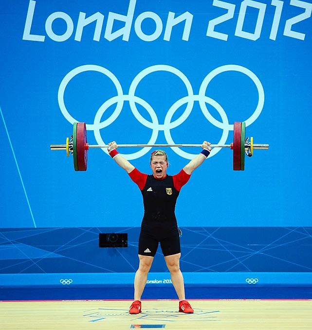 German Christin Ulrich yells as she hoists the bar above her head in the women's 58kg weightlifting event.