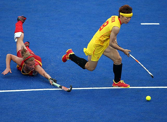 Belgium's Gaelle Valcke dives for the ball as opponent Baorong Fu of China slips by her during their women's field hockey match that ended in a 0-0 tie.
