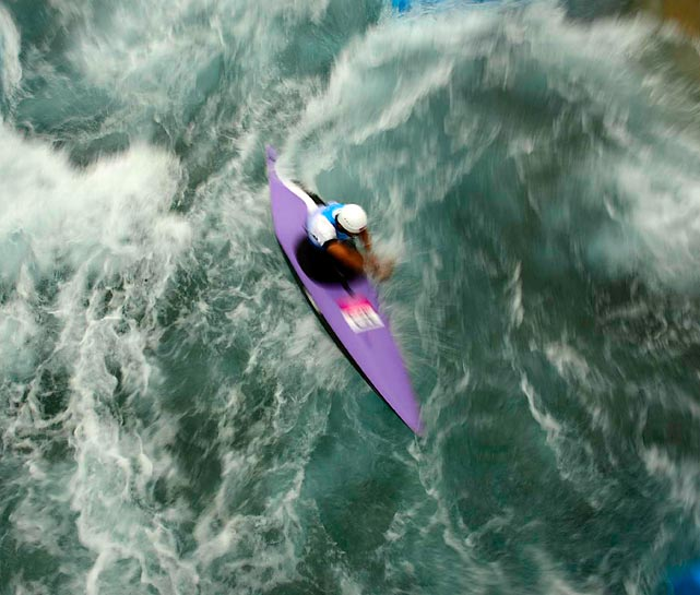 A canoeist fights against the rapids during the men's canoe slalom single semifinal and final.