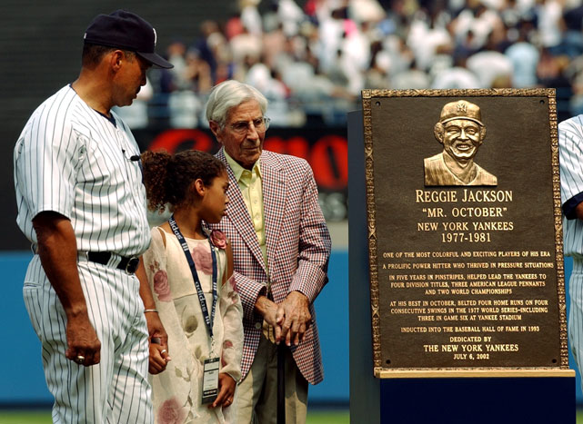 Hall of Famer Reggie Jackson, daughter Kimberly and Phil Rizzuto pose with the plaque, commemorating Jackson, placed in Yankee Stadium's Monument Park in 2006.