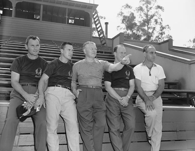 The coaching staff of the Redskins, from  left to right: Larry Siemering, line coach; Bill Dudley, backfield coach; Earl (Curly) Lambeau, head coach; Herman Ball, assistant coach; and Wayne Millner, assistant coach and scout.  They are picture here looking over a team workout at Occidental College in preparation for their charity game against the Los Angeles Rams on August 19th.