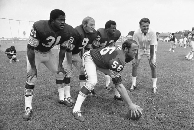Running back Charlie Harraway (31), quarterback Sonny Jurgensen (9), running back Larry Brown (43), and center Len Hauss (56) pose with new coach George Allen during the Redskins training camp.