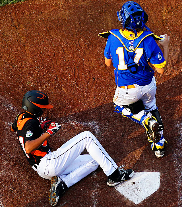 Taoyuan County, Taiwan's Kai-Chun Lin scores past Ramstein, Germany catcher Kyle Glenn on a fielder's choice by Chun-En Lin during the third inning of their pool play game.