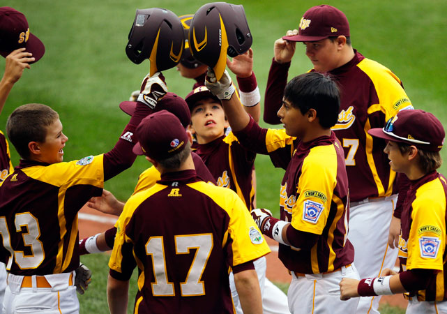 San Antonio, Texas' Zachary Sanchez (third from right) celebrates with teammates after hitting a two-run home run in the first inning against New Castle, Ind.