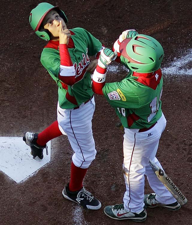 Mexico's Joel Turrubiates, left, and Marcelo Perez celebrate after Turrubiates' three-run home run in the second inning. Mexico scored five in the second and seven in the third to eliminate Uganda.