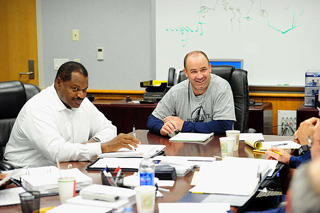 Penn State coach Bill O'Brien cracks a joke during a staff meeting. To O'Brien's right is defensive line coach Larry Johnson Sr. Johnson is one of only two assistants retained from Joe Paterno's staff.