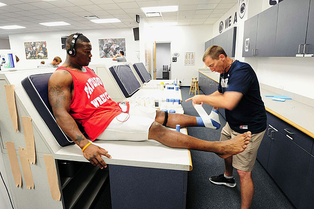 Penn State trainer Tim Bream tapes the ankles of linebacker Gerald Hodges. Bream, a Penn State graduate, worked for the Chicago Bears for 15 years before he was hired at his alma mater in February.