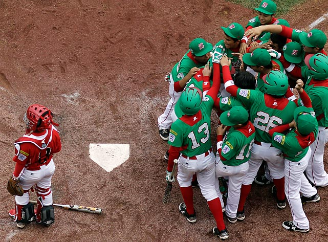 Mexico players mob Ramon Ballina at home plate after he hit a home run against Canada at the Little League World Series. Canada's catcher Ataru Yamaguchi, left, avoids the scene.