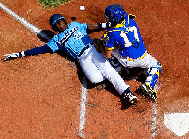 A wild throw on a stolen base allows Curacao's Shendrik Apostel to slide past Germany's Kyle Glenn to score at the Little League World Series.